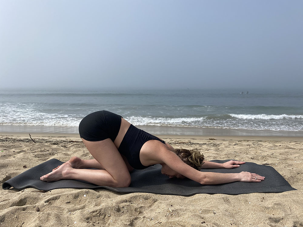 Uttana Shishosana - extended puppy melting heart pose - yoga pose girl sunny day yoga on the beach